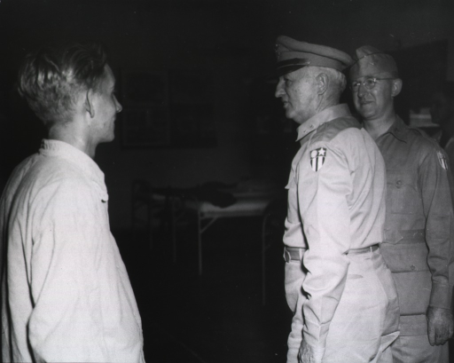 <p>Two unidentified military men chat with a young man who appears to be a patient.  In the background are hospital beds.</p>