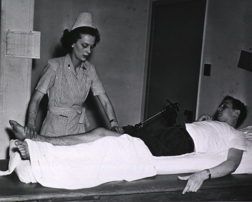 <p>Nurse giving soldier reeducational exercise for wounded leg.</p>