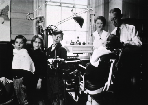 <p>View of a dentist, a nurse, and four children, one of whom is sitting in the dental chair in the office.</p>