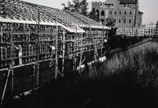 <p>Men are shown at work on a partially-constructed building.  In the background is another multi-story building.</p>
