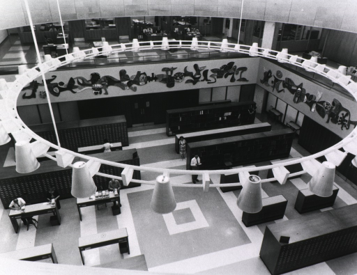 <p>View of the rotunda from the mezzanine that includes researchers using the card catalog, offices on the mezzanine, a partial view of the mural, some of the card catalog, and shelves of reference works.</p>