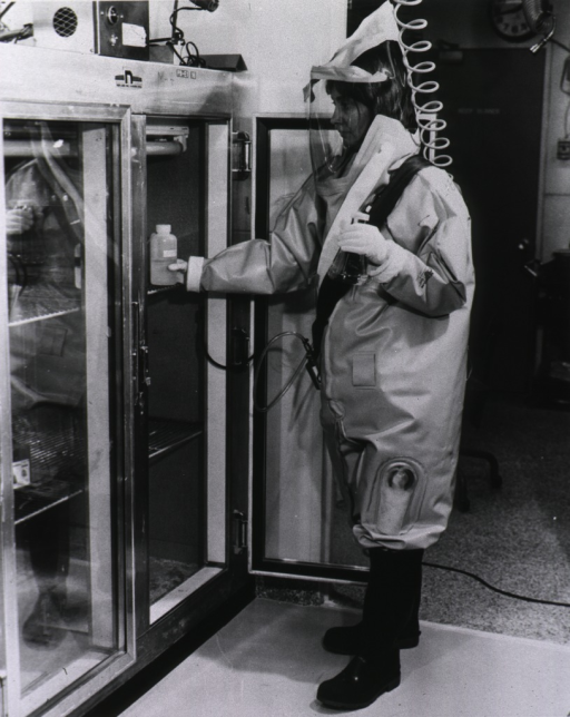 <p>A woman in a contamination suit places bottles in a refrigerator.</p>