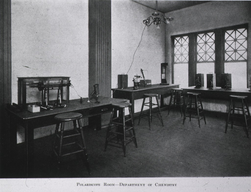 <p>Interior view: there are three tables with stools; equipment on the tables include a polariscope, a spectroscope, two refractometers, and several microscopes.</p>