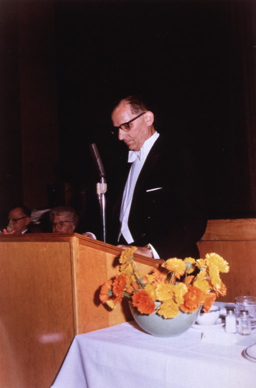 <p>Half length, left profile; wearing glasses; standing at lectern at a dinner.</p>