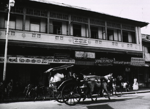 <p>Exterior view: street scene showing two-story building with several shops on the ground floor and the surgical clinic on the second floor; many children are seen on the sidewalk; a horse-drawn carriage is headed up the street.</p>