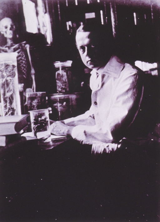 <p>Half-length, seated at desk, body in left profile, face front; wearing white lab coat; jars of preserved specimens on desk, skeleton in background.</p>