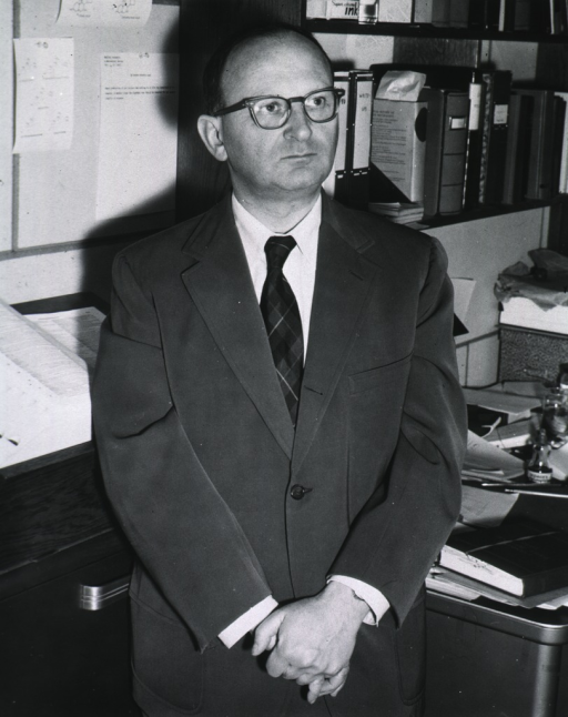 <p>Half-length, full face, standing beside his desk, hands clasped.</p>