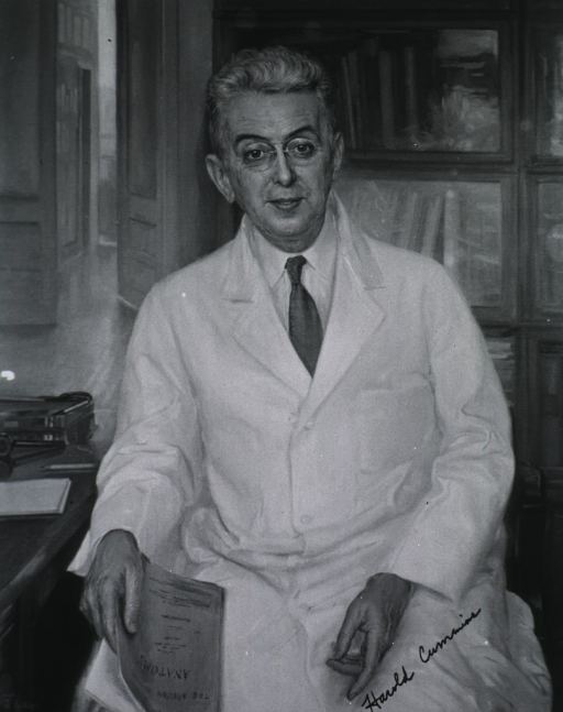 <p>Three-quarter length, seated in office, full face, wearing lab coat.</p>