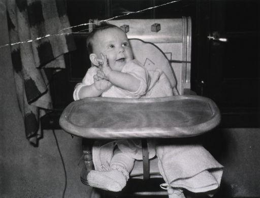 <p>View of a happy, smiling baby sitting in a highchair.</p>