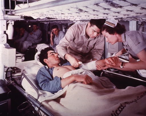 <p>Nurse and corpsman attending wounded below deck.</p>