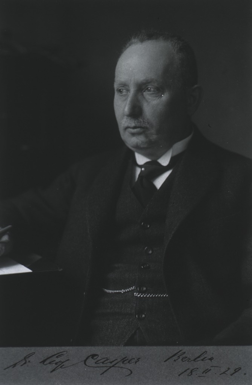 <p>Left pose, seated at desk.</p>
