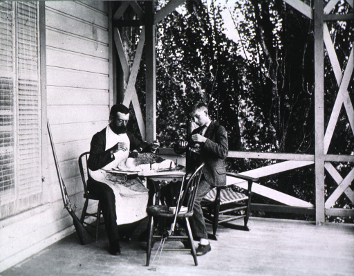 <p>Seated at table with young man, engaged in scientific ornithology.</p>