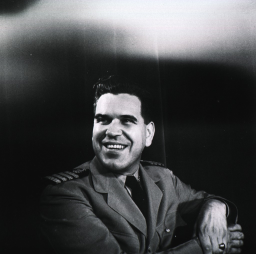 <p>Head and shoulders, seated, right pose, full face; wearing uniform; arm over back of chair; hands together.</p>