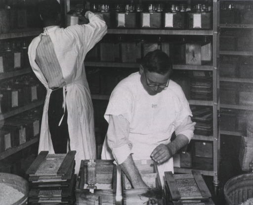 <p>The mesh side of the cage is removed and stacked to the side.  One man's hand is inside a cage.  The other man, an African American, is moving a cage on the shelf.</p>