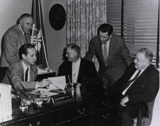 <p>L.E. Burney, M.D. sits and his desk in his office and looks through papers. He is surrounded by four unidentified men in suits.</p>