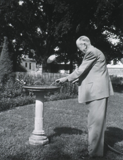 <p>Full length, left profile, standing, holding water hose over bird bath.</p>