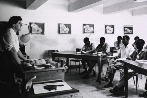 <p>Interior view of a classroom: a woman instructor is teaching midwifery techniques to several medical assistants.</p>