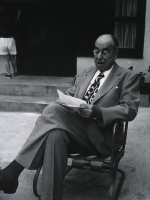 <p>Full length, seated in front of house, legs crossed, reading letters.</p>