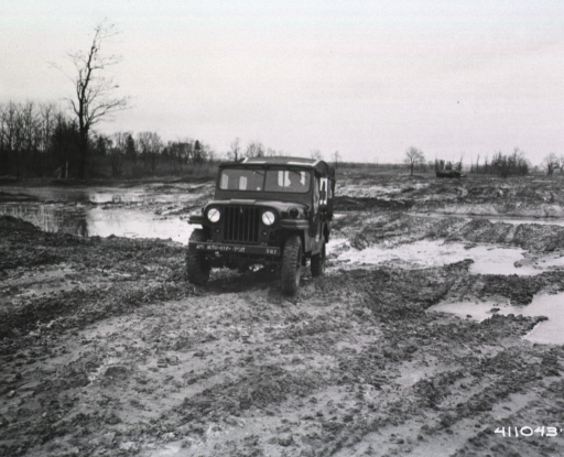 <p>An ambulance jeep is driven across a muddy field by a serviceman.  In the distance, another military vehicle can be seen idling.</p>
