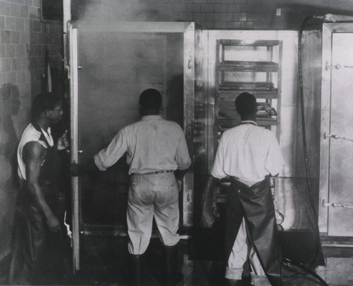 <p>Three African Americans are standing in front of a wall that has a metal shelf between two floor-to-ceiling containers.  Two men are wearing rubber aprons.  The man in the middle is wearing rubber boots.</p>