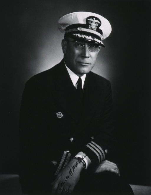 <p>Seated, full face, hands crossed, naval uniform, cap; commander.</p>