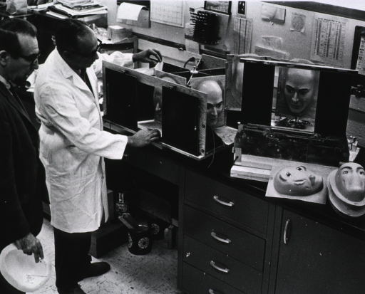 <p>Publicity photo.  Dr. Albert Caron and Larry Sator, engineering technician of the Technical Development Section, discuss the problems in constructing the device, shown here, for producing models of various facial expressions.</p>