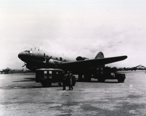 <p>Two ambulances are next to a transport airplane.  Military personnel hover around the vehicles.  In the background are other planes.</p>