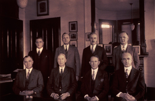 <p>Hugh S. Cumming was surgeon general from 1920-1936.  Seated from left to right are Arthur M. Stimson, Hugh Smith Cumming, Claude Connor Pierce, and Fredrick C. Smith.  Standing behind them are Warren Fales Draper, Ralph Chester Williams, Thomas Parran and an eighth member of the Surgeon General's staff.  They are in front of what appears to be a fireplace.  A large mirror is above this fireplace's mantel.  The mirror reflects a bay window with shades drawn and a ceiling light. Pictures are on the wall behind Drs. Williams and Parran, on the mantel, and over the doorway.  There is a Harriman &amp; Co. directory and a closed book with papers inside on the table to Dr. Stimson's right.</p>