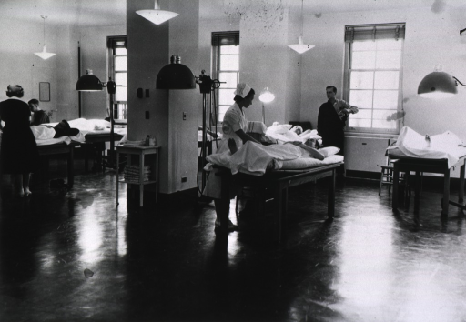 <p>Interior of ward, nurses assisting patients.</p>