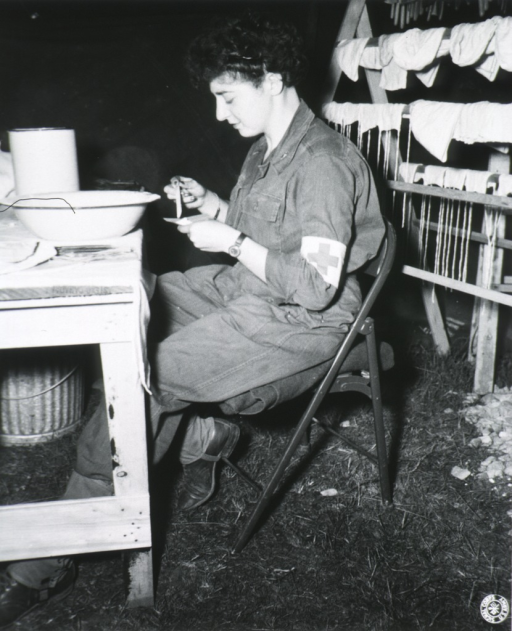 <p>Full length, seated at table, left profile; wearing uniform with Red Cross arm band.</p>