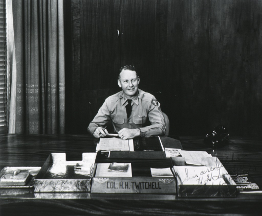 <p>Seated at desk; full face, uniform, col., holding pencil.</p>