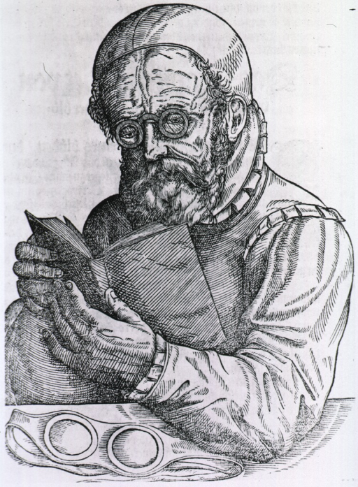 <p>A man sits at table reading a book, he is wearing spectacles; a pair of protective lenses are on the table.</p>