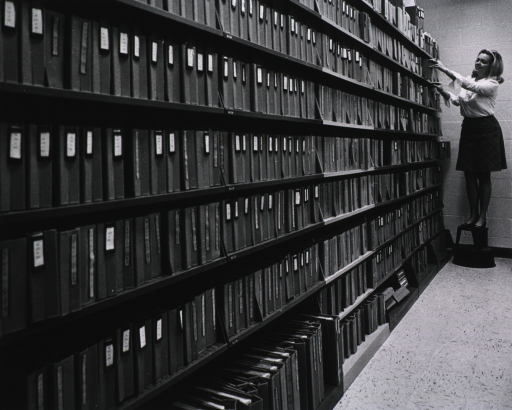 <p>Publicity photo.  Nancy Johnson is shown retrieving a binder containing the record of a drug that has been tested against cancer.  On the shelves are the reports of more than 200,000 compounds tested.</p>