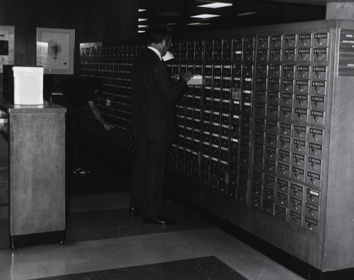 <p>Interior view: Two men are using the name catalog for material in the range of &quot;shas-z&quot;.</p>