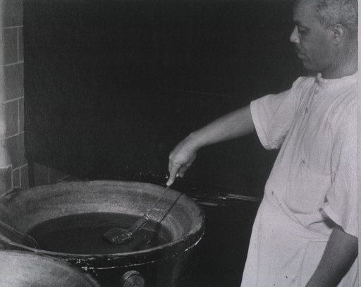 <p>An African American man is using a long handled tool to place a beaker in a container's solution.  The container has a thermostat on its side.</p>
