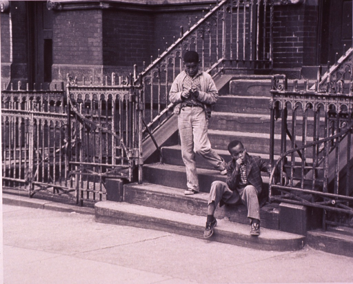 <p>Two children on the steps to an inner city school building.</p>