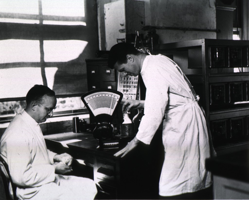 <p>Three-quarter length, in PHS laboratory with Dr. H. Frank Fraser seated to his left.</p>