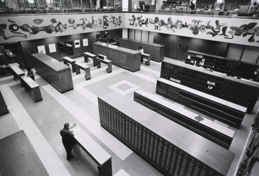 <p>View of the rotunda from the mezzanine that includes the bibliographic services division, a partial view of the mural, some of the card catalog, and shelves of reference works.</p>