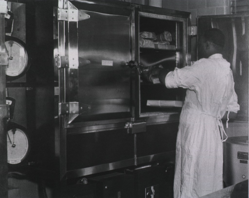 <p>An African American is placing a wrapped package on a shelf in a refrigeration unit</p>
