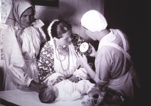 <p>Nurse with a clock, instructing a mother with a baby, in Mraklin, Yugoslavia.  One of a collection of pictures from 1928 depicting the early Public Health Organization.</p>