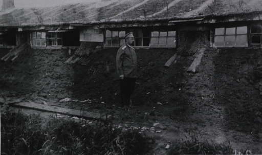 <p>An officer stands outside a sod building at Military Mobile Hospital No. 45.</p>
