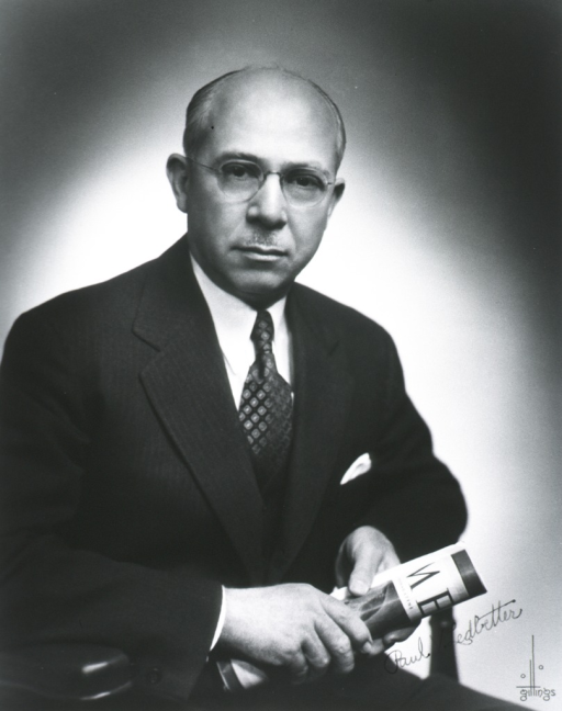 <p>Half-length, seated, right pose, full face; wearing glasses; holding magazine.</p>