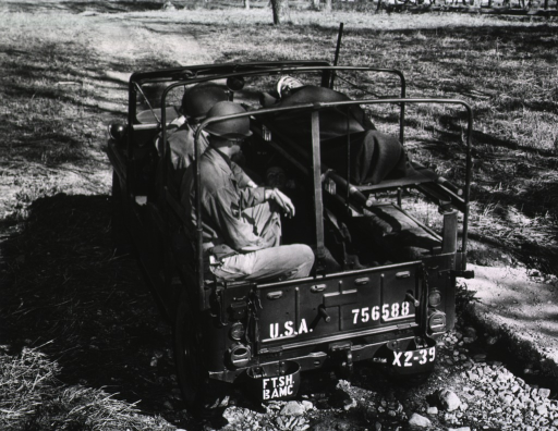 <p>The open-air jeep is parked in a field.  On one side of the bed of the jeep, three servicemen sit facing the two litters positioned one on top of the other on the other side of the jeep's bed.  In each litter, a serviceman lies on his back and is covered with a blanket (cf. no. 17, which is another view of the same subject).</p>