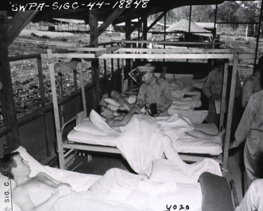 <p>Several wounded servicemen lie in beds and watch as Gen. Denit presents a medal to one of the servicemen.  Other military personnel stand at the foot of the bed and watch.</p>