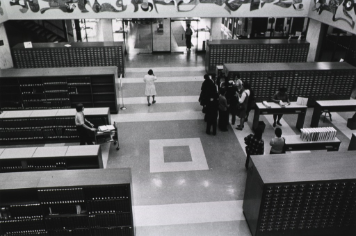 <p>View of the rotunda that includes reference works, the card catalog, and the doorway leading to the main entrance.  The circulation desk is in the background.</p>