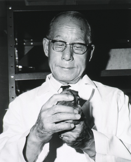 <p>Head and shoulders, full face; wearing white coat and glasses; holding hamster(?).</p>