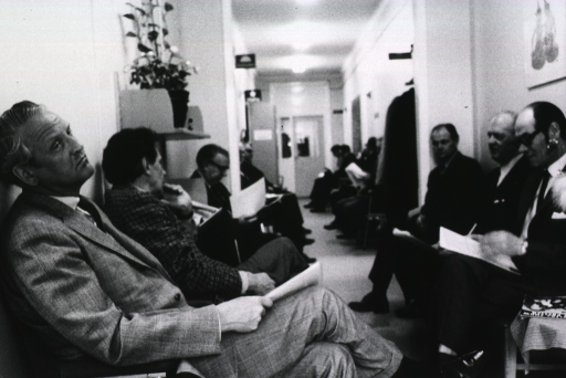 <p>Interior view of a waiting room showing several men sitting in chairs.</p>