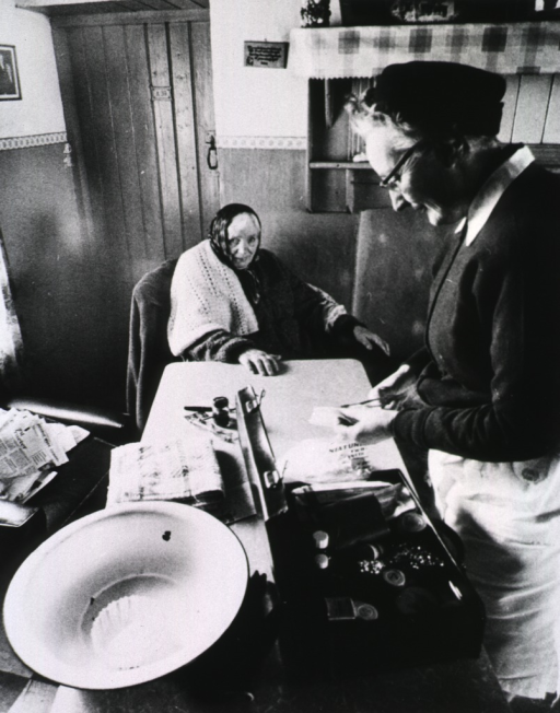 <p>Interior view of a residence: an elderly woman is preparing to treat another elderly woman sitting in a chair at the end of a table. The health worker's medical bag is on the table.</p>