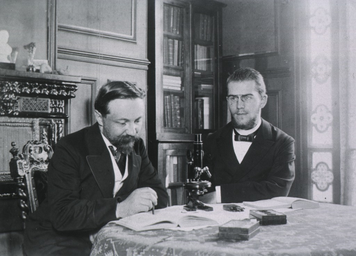 <p>Half-length, seated at table with microscope and unidentified person.</p>