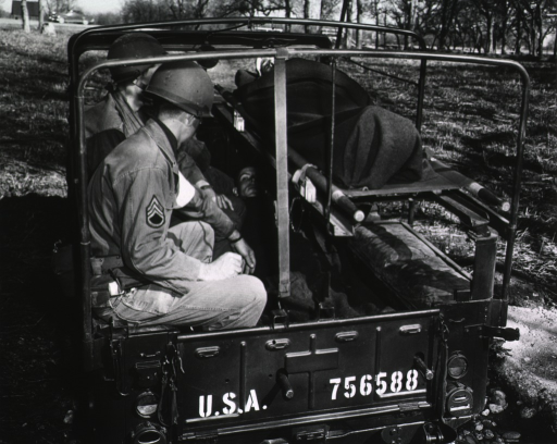 <p>The open-air jeep is parked in a field.  On one side of the bed of the jeep, three servicemen sit facing the two litters positioned one on top of the other on the other side of the jeep's bed.  In each litter, a serviceman lies on his back and is covered with a blanket (cf. no. 16, which is another view of the same subject).</p>